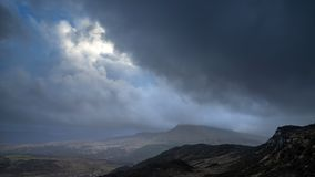 Moody and dramatic Winter landscape image of Moel Saibod from Crimpiau in Snowdonia with stunning shafts of light in stormy stock photography