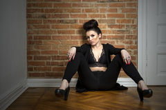 Moody elegant woman sitting on a parquet floor Royalty Free Stock Images
