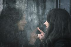 Woman and her reflection on rainy window. Moody image with a young woman sitting in front of a rainy window and touching it with its finger Stock Images