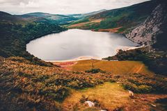 Moody landscape of hills and lake in Wicklow Mountain, Ireland. Small lake surrounded by dark green and orange hills on moody, gloomy, cloudy day. Wicklow stock photo
