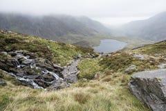 Landscape image of Llyn Idwal in Glyders mountain range in Snowd. Moody landscape image of Llyn Idwal in Glyders mountain range in Snowdonia during heavy stock image