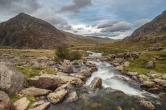 Moody landscape image of river flowing down mountain range near royalty free stock images