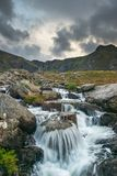 Moody landscape image of river flowing down mountain range near. Landscape image of river flowing down mountain range near Llyn Ogwen and Llyn Idwal in Snowdonia stock photography