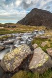 Moody landscape image of river flowing down mountain range near stock photo