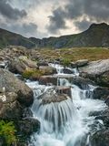 Moody landscape image of river flowing down mountain range near. Landscape image of river flowing down mountain range near Llyn Ogwen and Llyn Idwal in Snowdonia stock photos