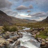 Moody landscape image of river flowing down mountain range near. Landscape image of river flowing down mountain range near Llyn Ogwen and Llyn Idwal in Snowdonia royalty free stock images