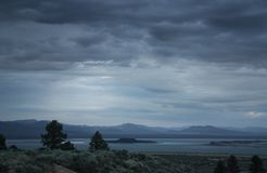 Moody landscape with a storm rising over a lake stock photos