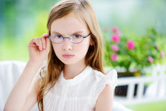 Moody little girl wearing eyeglasses feeling angry and unsatisfied. Children tantrum concept Stock Photos
