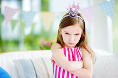 Moody little girl wearing princess tiara feeling angry and unsatisfied. Children tantrum concept Royalty Free Stock Images