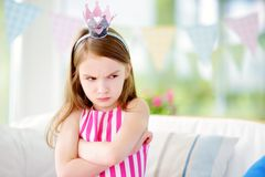 Moody little girl wearing princess tiara feeling angry and unsatisfied. Children tantrum concept Royalty Free Stock Photography