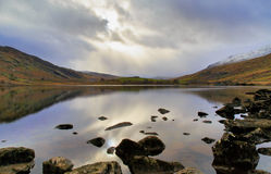 Moody Llyn Mymbyr Snowdonia. Sun light highlighting storm clouds reflected in Moody Llyn Mymbyr Snowdonia Wales Stock Images