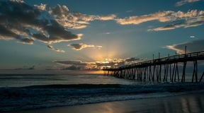 Dramatic sunrise lights up the clouds and sunbeams burst from the clouds. An old wooden ocean pier at sunrise. royalty free stock photo