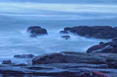 Moody Ocean Seascape landscape on rocky beach. Moody ocean seascape with landscape of rocky beach with cool blue tint Royalty Free Stock Image