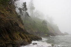 Moody Pacific Shoreline, a rocky cliff in fog Stock Photos
