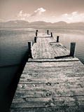 Moody pier. A duo-tone picture of an old wooden pier with mountains in the background stock image