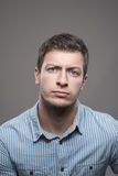 Moody portrait of distrustful young executive man in blue shirt looking at camera Royalty Free Stock Images