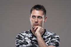 Moody portrait of pensive thoughtful man looking away thinking with hand on chin stock photo