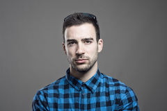 Moody portrait of skeptical young man frowning face looking at camera Royalty Free Stock Photo