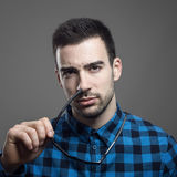 Moody portrait of skeptical young man taking off sunglasses looking at camera Stock Photo