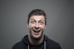 Moody portrait of surprised expressive young man looking at camera Royalty Free Stock Images