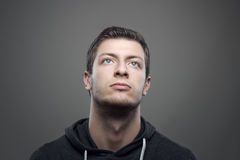 Moody portrait of young casual man looking up with illuminated face Royalty Free Stock Photo