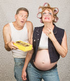 Moody Pregant Lady and Man. Moody redneck hillbilly pregnant couple with candy Royalty Free Stock Photo