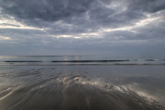 Moody ramatic sky reflected on wet beach landscape Royalty Free Stock Images
