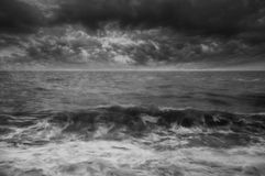Moody seascape of waves breaking UNDER STORMY wINTER SKY Stock Photography