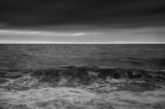 Moody seascape of waves breaking UNDER STORMY wINTER SKY Royalty Free Stock Photo