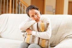 Moody senior woman sitting on sofa Royalty Free Stock Image