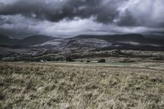 Moody sky with rainclouds over beautiful mountain valley in Lake District, UK. Dark, dramatic sky with rainclouds over beautiful mountain valley with sunlight stock photo