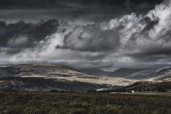 Moody sky with rainclouds over scenic mountain valley in Lake District, UK. Dark, dramatic sky with rainclouds over scenic mountain valley with sunlight painting stock image