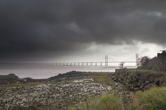 Moody skys the Severn Estuary. Moody Skys over The Second Severn Bridge Boarder Crossing, Low tied exposing mud and rock flats Stock Image