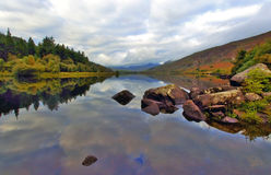Moody Snowdonia reflected in Peaceful Llyn Mymbyr Snowdonia. Moody Snowdonia reflected in Peaceful Llyn Mymbyr Capel Curig Snowdon Wales Royalty Free Stock Photography