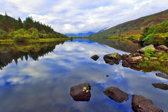 Moody Snowdonia reflected in Peaceful Llyn Mymbyr Snowdonia. Moody Snowdonia reflected in Peaceful Llyn Mymbyr Capel Curig Snowdon Wales Stock Photo