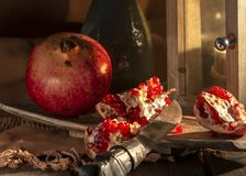 Pomegranate food still life picture. A moody still life picture with a landern and highlighted pomegranates stock photography