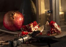 Pomegranate and lantern still life picture. A moody still life picture with a landern and highlighted pomegranates royalty free stock image