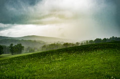 Moody Stormy Landscape. Field with mountains in background summer Stock Image