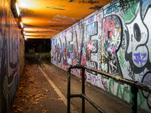 Moody Subway with Graffiti in Bristol. Moody and urban subway with graffiti artwork, lit by sodium lamps in Bristol Stock Image