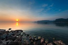 Moody sunset at lake gardasee. With rocks at coast Royalty Free Stock Images