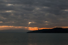 Moody sunset on a lake. A moody sunset on a lake, with a silhouette of an island with some buildings and towers, and an overcast sky with a single sunray coming Stock Photography