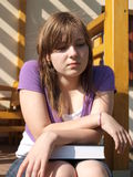 Moody teenager. Sitting with book Stock Images