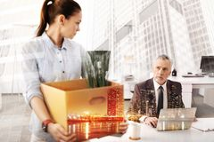 Moody unemployed woman looking at her strict boss. Time to say good bye. Depressed unemployed young women holding the box with her belongings and looking at her royalty free stock photography