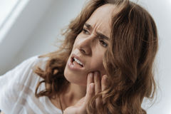 Moody upset woman having a tooth inflammation. Pain in the tooth. Moody upset unhappy woman holding her cheek and thinking about visiting a dentist while having Stock Photos