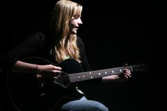 Moody woman playing guitar and singing Royalty Free Stock Images