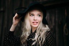 Mooi aantrekkelijk en modieus meisje die het zwarte hoed bevindende stellen in stad dragen Naakte make-up, het best dagelijks kap Royalty-vrije Stock Foto