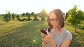 Mooi aantrekkelijk meisje die op haar smartphone met vriend babbelen Haar die in de zomerwind fladderen stock footage