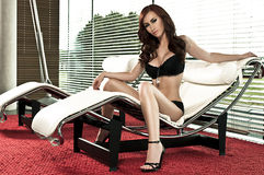 Mooi aantrekkingskrachtmeisje op zitkamerstoel Royalty-vrije Stock Afbeeldingen