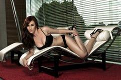Mooi aantrekkingskrachtmeisje op zitkamerstoel Stock Afbeeldingen
