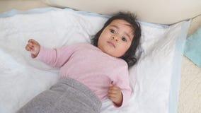 Mooi Afrikaans Amerikaans klein halfjaarlijks oud babymeisje op bed stock footage